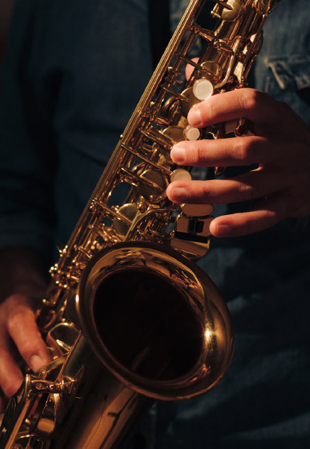 A close-up of hands playing a saxophone in a night club