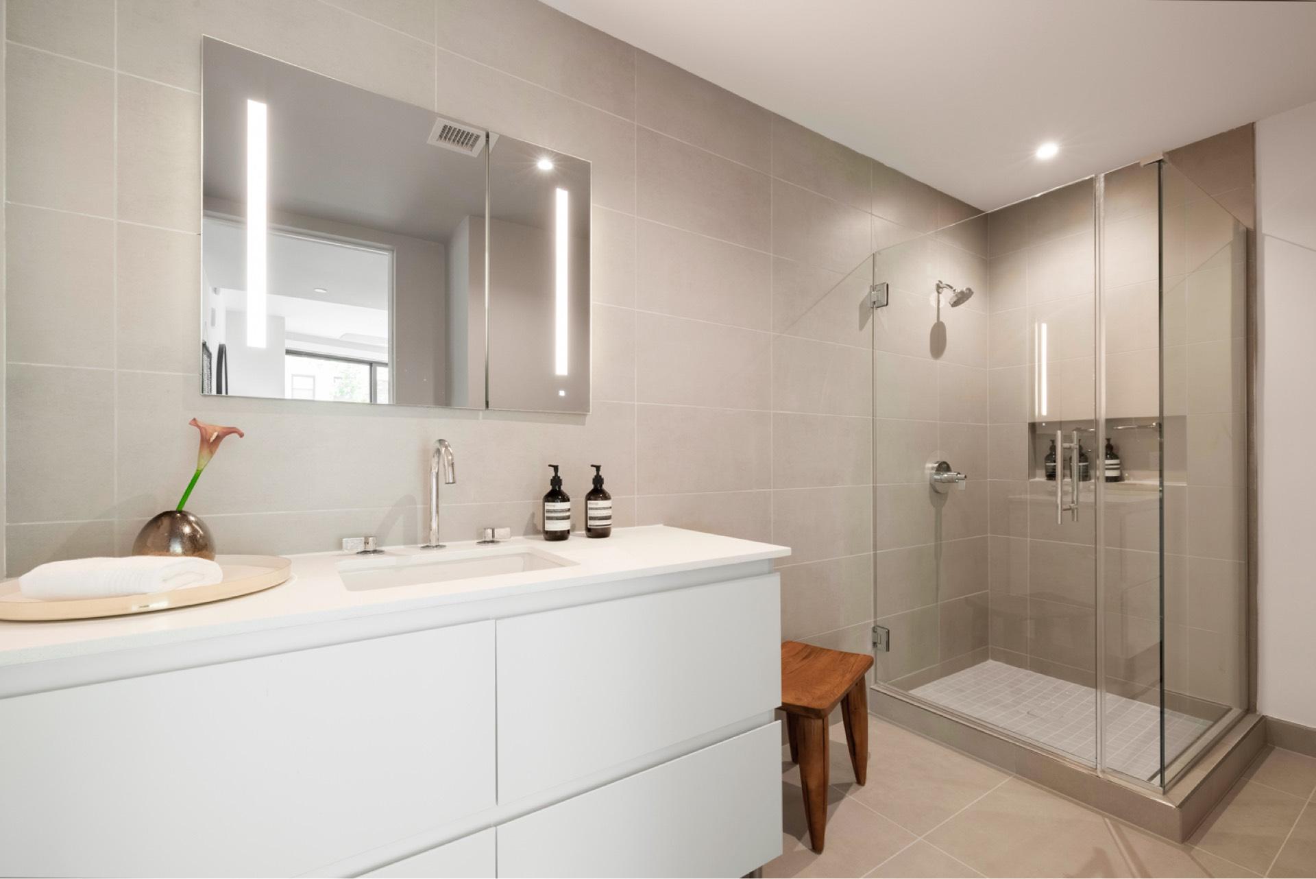 Porcelanosa® tile, Robern® medicine cabinets, and Kohler® fixtures in bathrooms